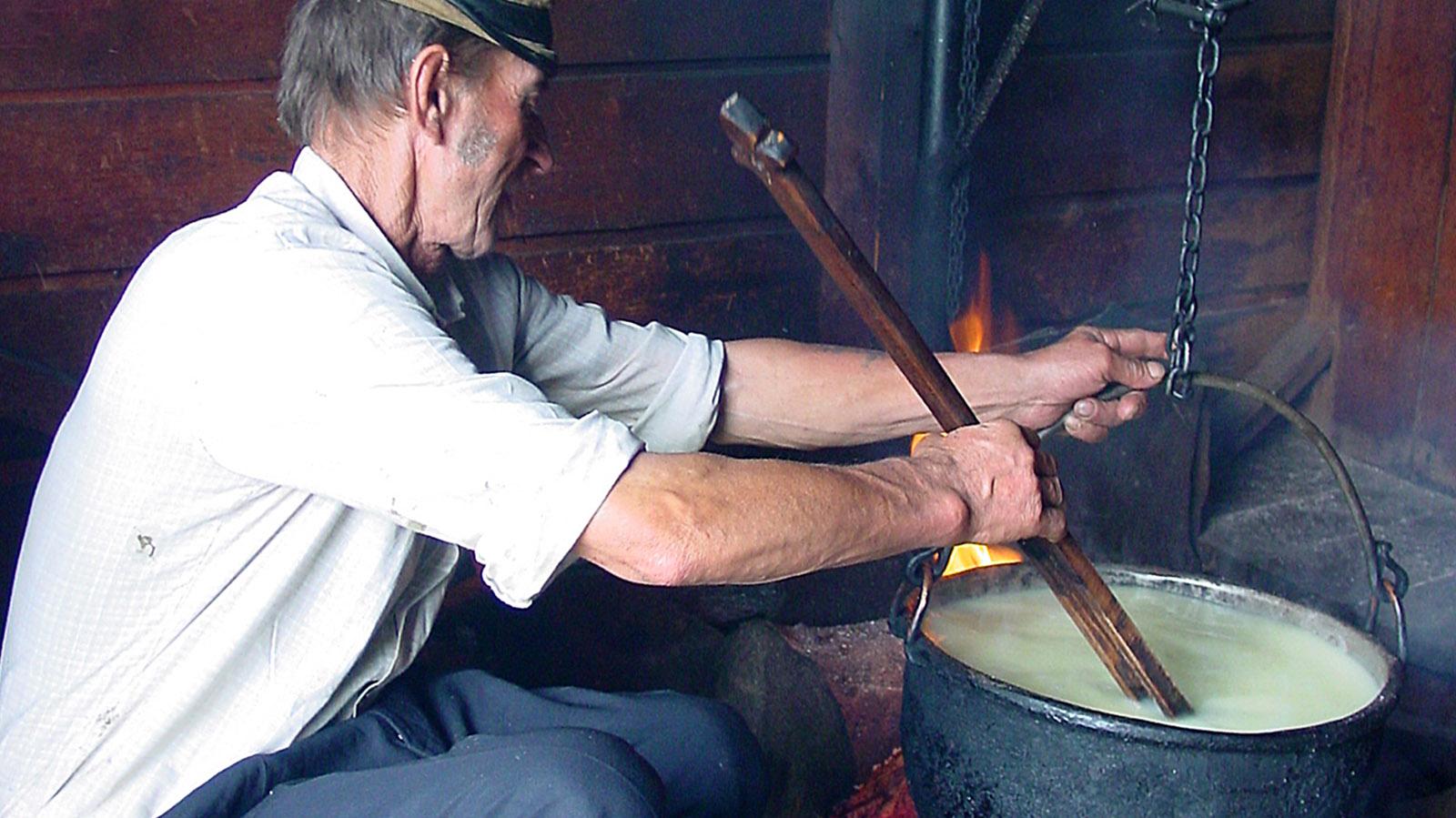 """Jan Urbas bei der Käsefertigung. In der Hand: der geräucherte Hartkäse aus Schafsmilch """"Oscypek"""" - eine regionale Spezialität. Foto: Hilke Maunder"""