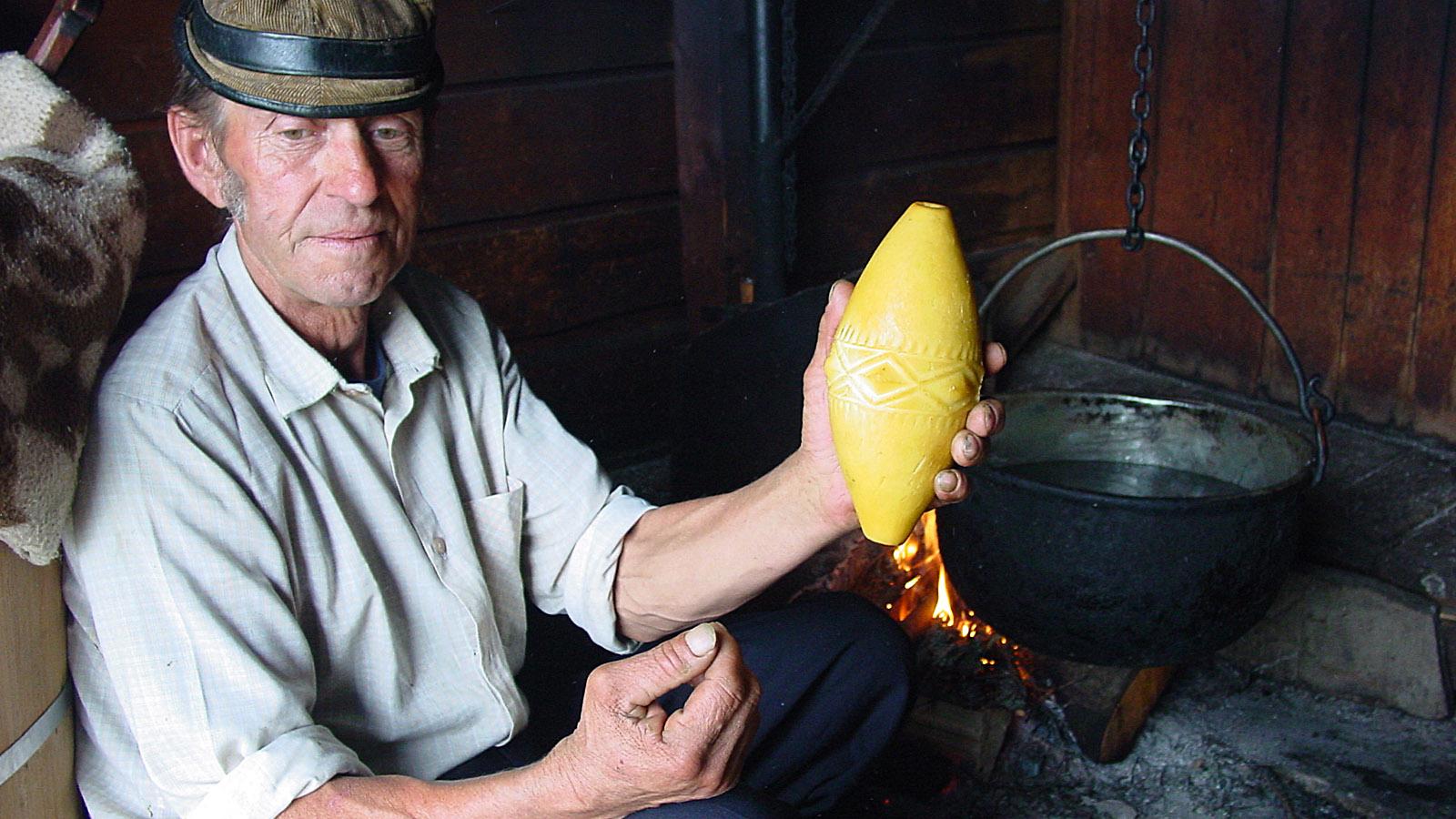 """Hohe Tatra, Jan Urbas bei der Käsefertigung. In der Hand: der geräucherte Hartkäse aus Schafsmilch """"Oscypek"""" - eine regionale Spezialität. Foto: Hilke Maunder"""