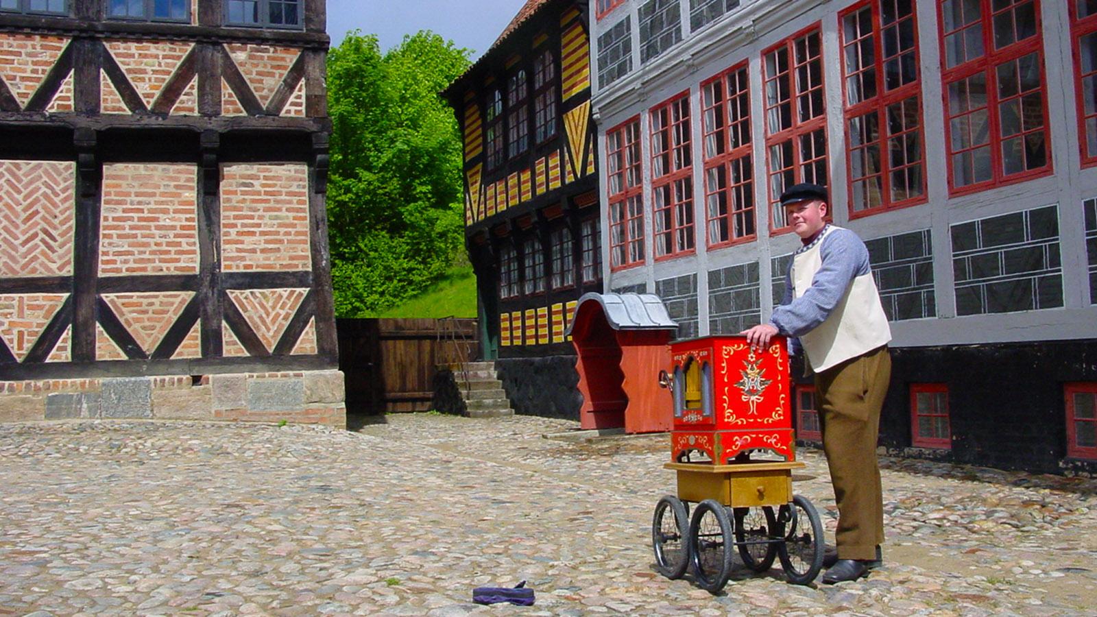 Den Gamle By: Im Sommer spielt ein Leierkastenmann vor den historischen Fassaden. Foto: Hilke Maunder