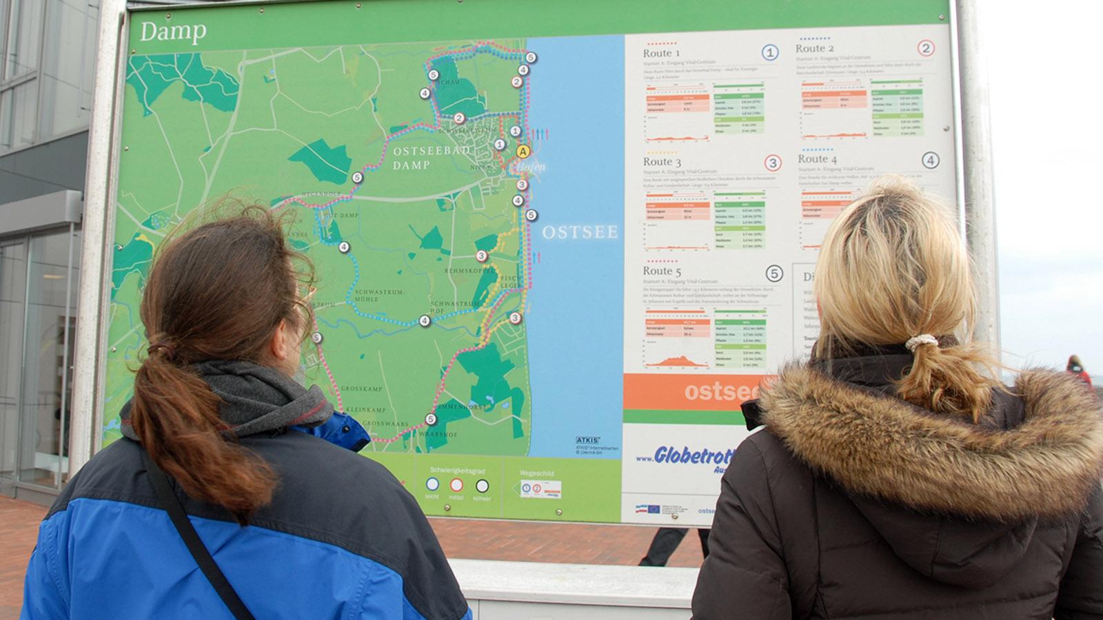Stephanie Kreuzer (l.) und Eva Ehmke (r.) informieren sich an einer Übersichtskarte über die Angebote in Damp. Foto: Hilke Maunder