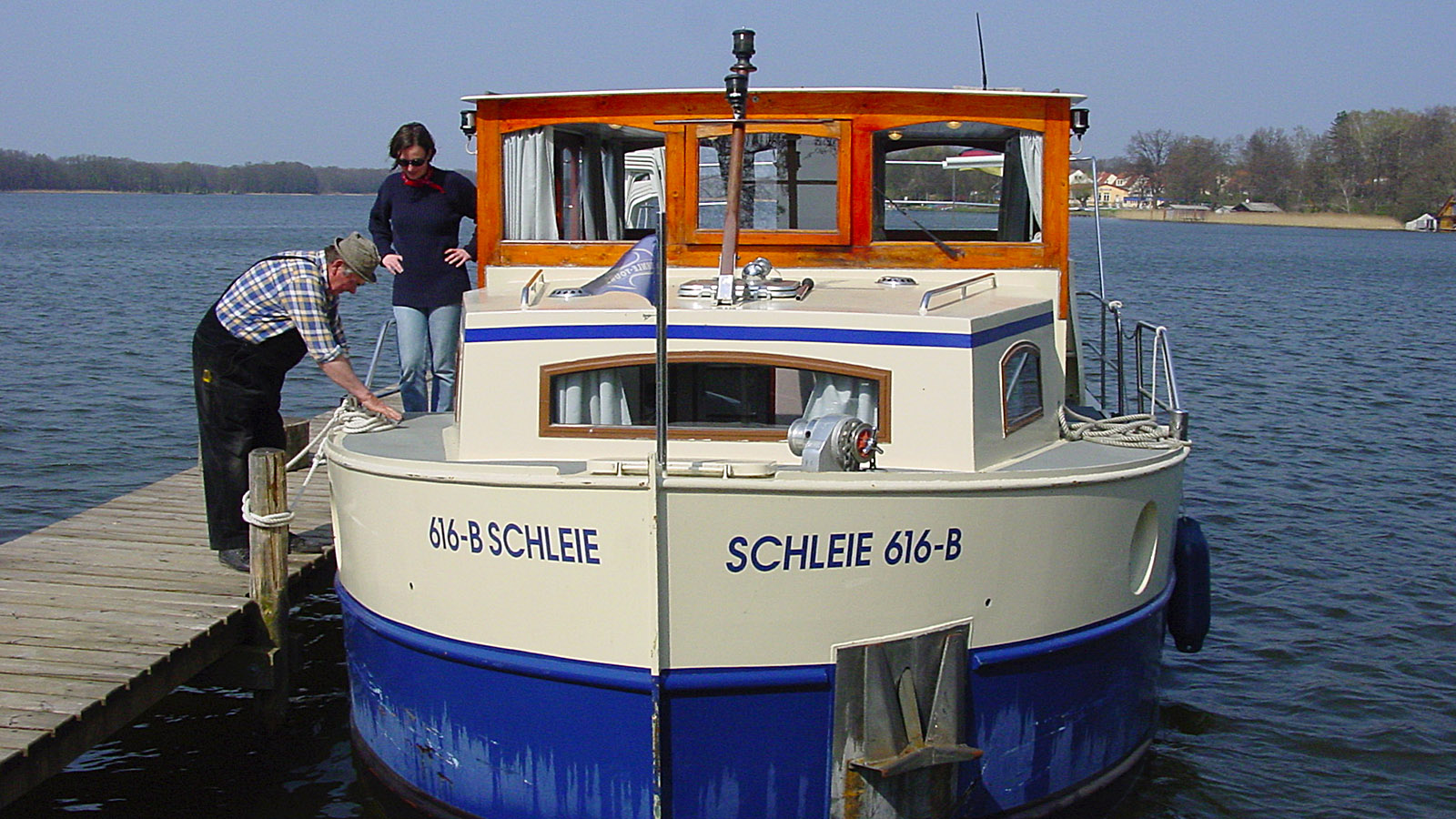 Hausboot-Törn in Mecklenburg. Horst Rick vertäut das 11-Meter-Hausboot am Bootssteg vor der Schlossinsel; Gesche Harm schaut zu. Foto: Hilke Maunder