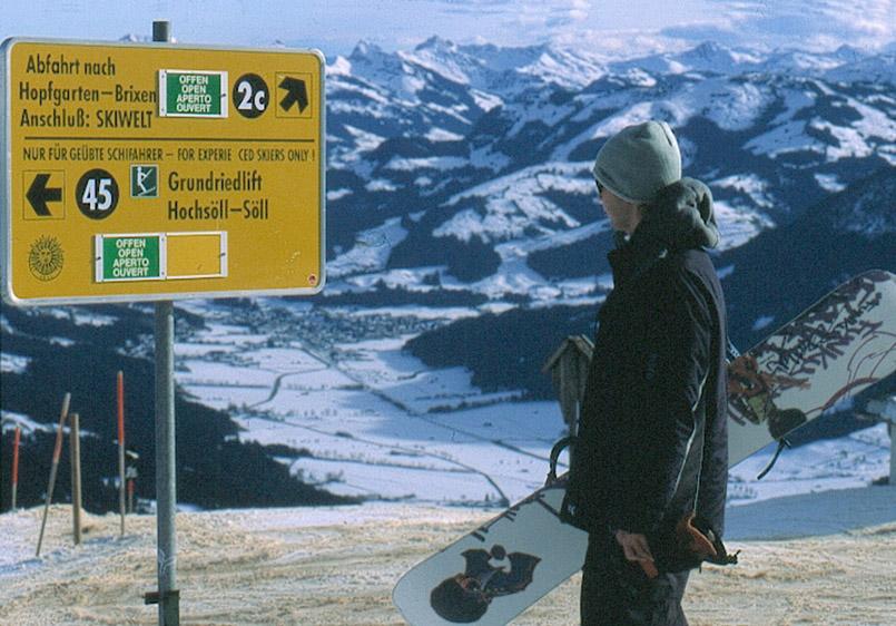 Skiwelt Wilder Kaiser: Hohe Salve, Abfahrten. Snowboarder betrachtet die Infotafel.