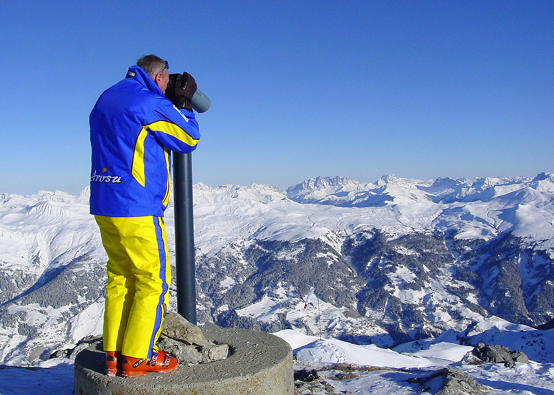Arosa/Skigebiet: Weißhorn-Gipfel, Skilehrer Paul blickt durch Fernglas.