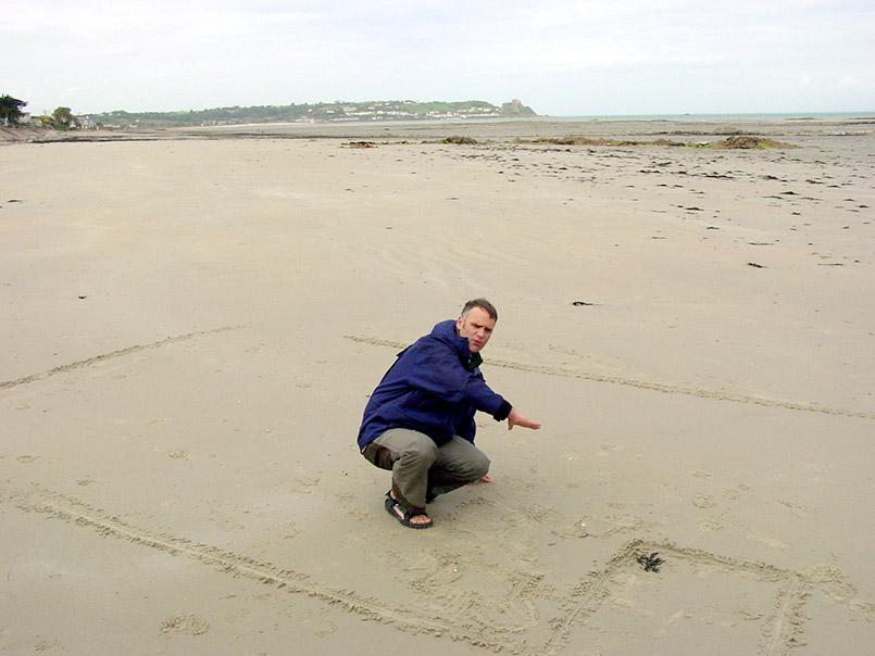 """GB/Jersey/Watt-Landschaft beim Seymour Inn an der Südostküste, zu entdecken bei """"Moon Walks"""". Hier: Guide Andrew Syvret erläutert im Sand die Meeresbewegungen und Gezeiten Jerseys."""