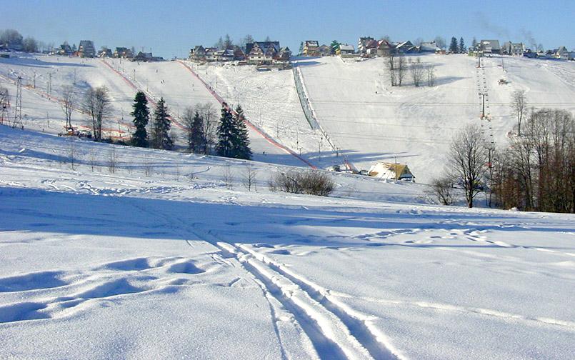 ukowina Tatrazanska: Im großen Halbrund führen die Pisten (sechs Lifte) mitten im Dorf hinab ins Tal.