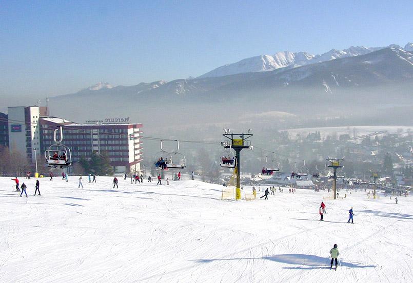 """Polana Szymoszkowa: Ein Sechser-Sessel, ein Vierersessel und ein paar Schlepplifte etwas abseits im Tal erschließen das Skifeld am Mercure-Hotel """"Kasprowy"""". Rings um die Bergstation gibt es mehrere Skihütten, die neben Grill-Schnacks und Suppen auch Glühwein (Wino grzana) und """"Glühbier"""" (Piwo grzana) anbieten."""