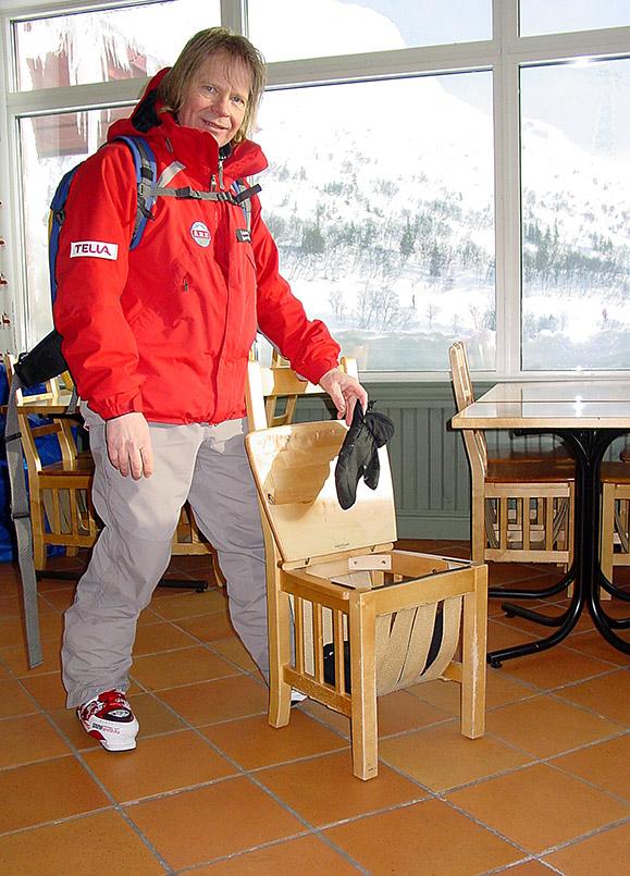 Are: Praktische Stühle im Café Olympia: das Netz unterhalb der klappbaren Sitzfläche nimmt Helm, Handschuhe, Skibrille und sonstiges auf. Skilehrer Esa (50/2005) zeigt das Prinzip.